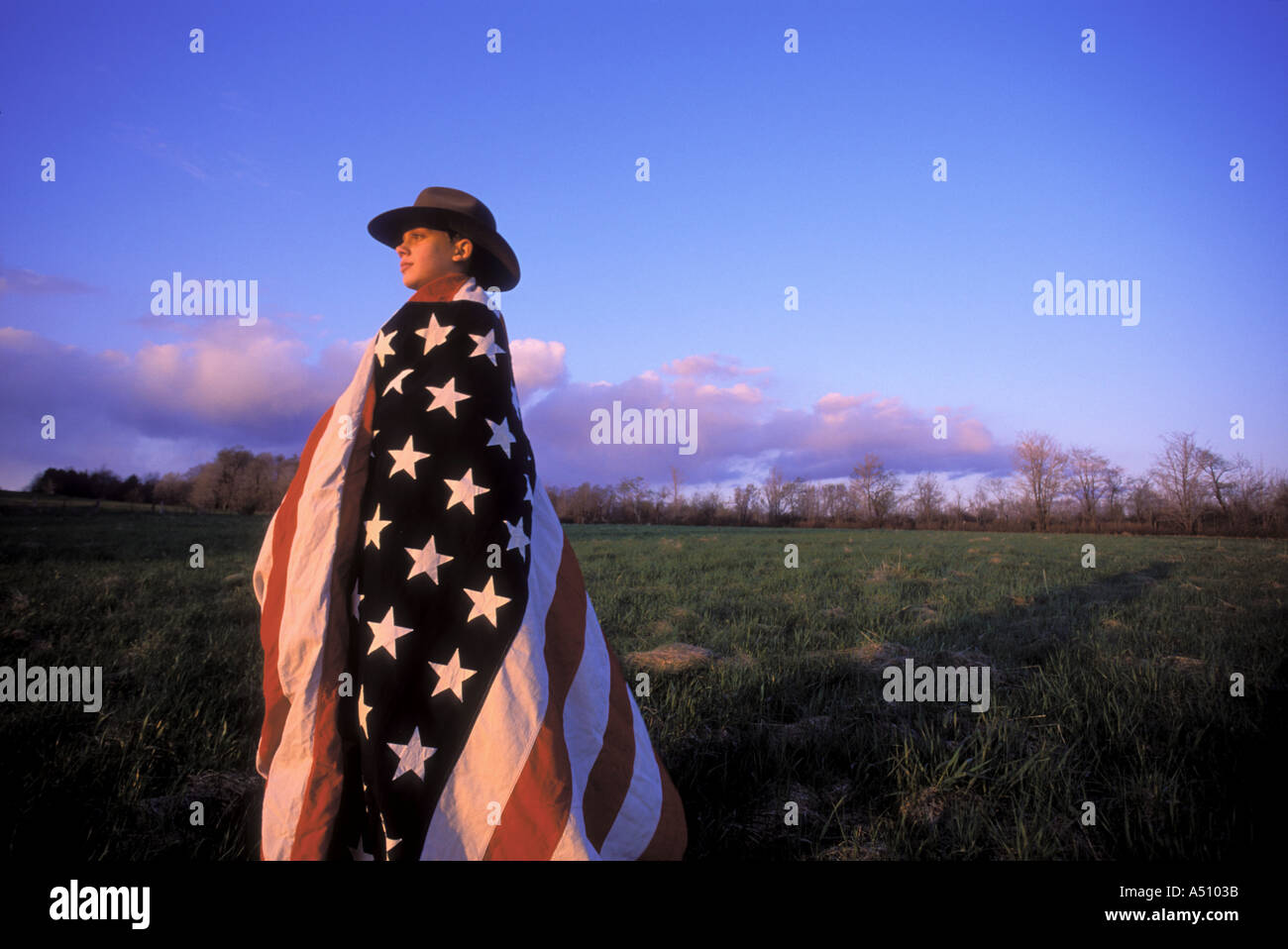 Boy in coyboy hat and wrapped in American flag standing in field at dusk looking toward horizon Upstate New York - Stock Image