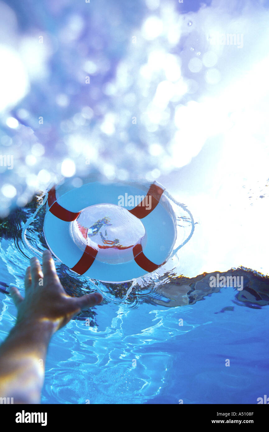 Swimmers hand reaching up toward life saving ring floating on surface of water - Stock Image