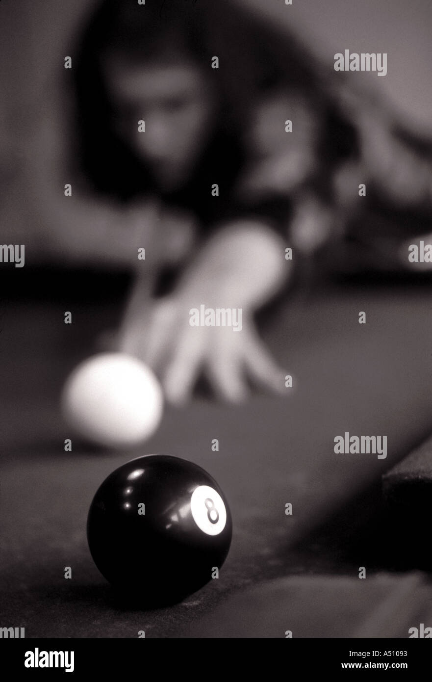 Man playing pool in a billiards hall Black and white image - Stock Image