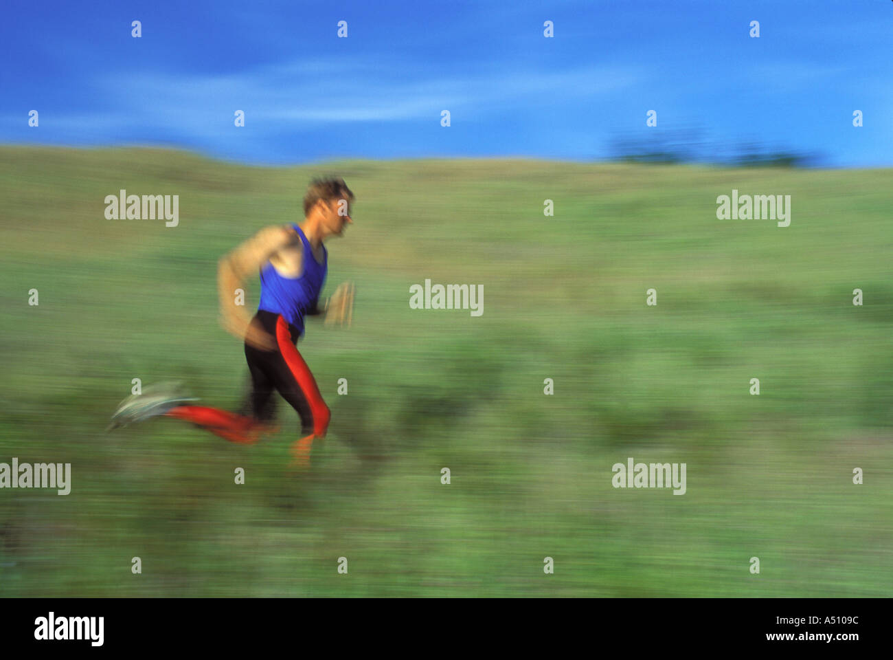 Blurred motion image of man running in field California USA - Stock Image