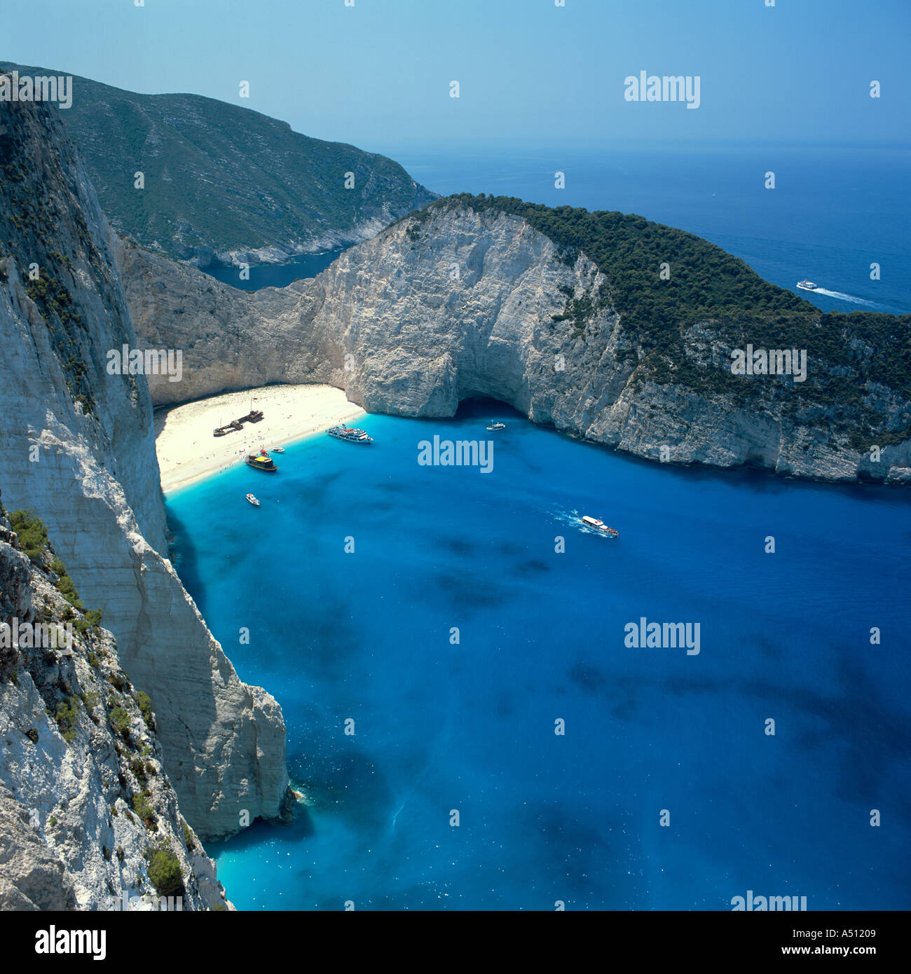 View down over spectacular Shipwreck Bay and steep cliffs with distant people on beach Zakynthos The Greek Islands - Stock Image
