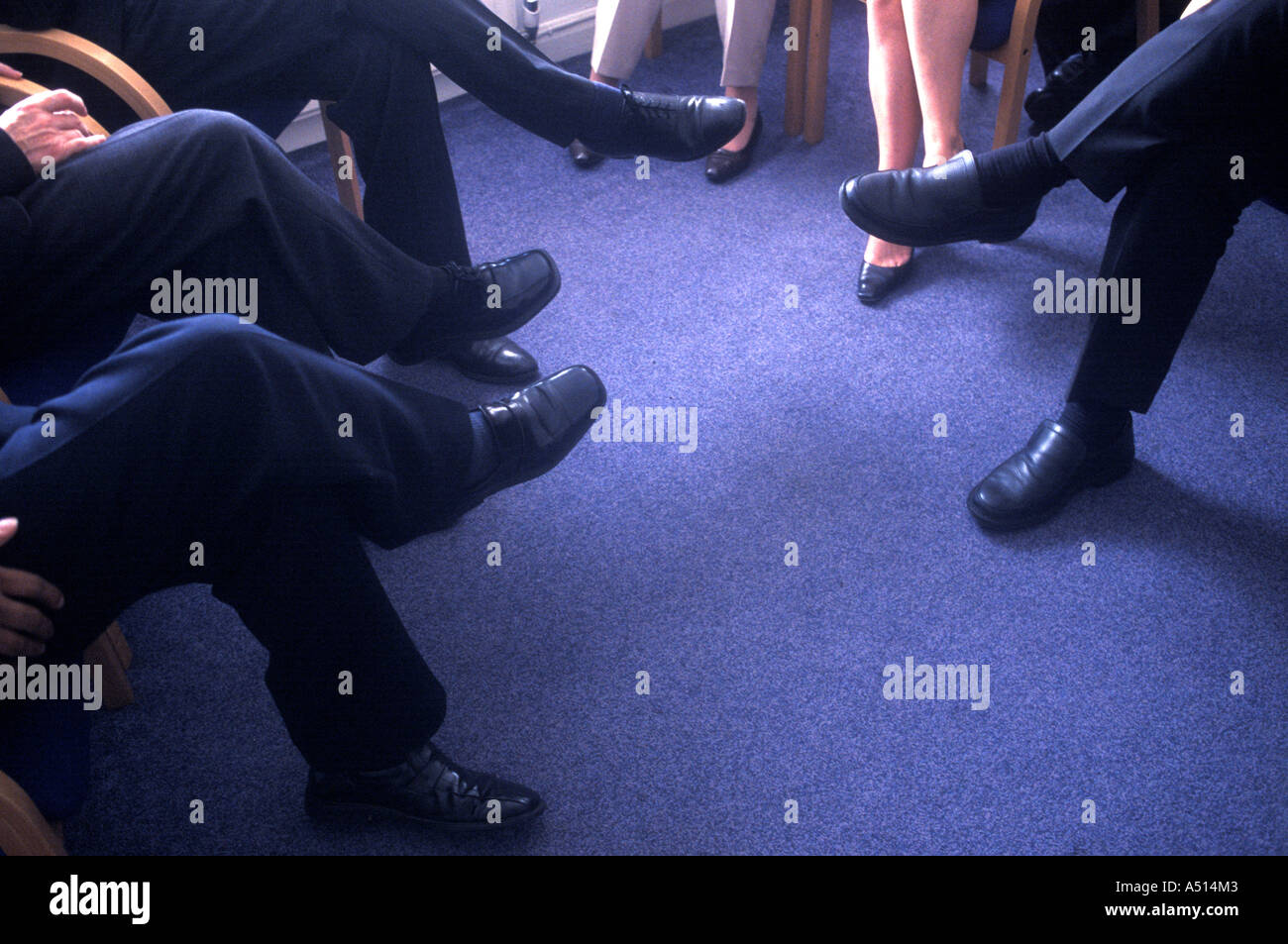 Shoes and legs of doctors and journalists at a press conference in London, UK. - Stock Image