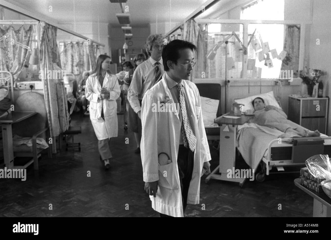 A Junior Doctor touring a hospital ward with colleagues and a senior doctor, Whipps Cross Hospital, London, UK. - Stock Image