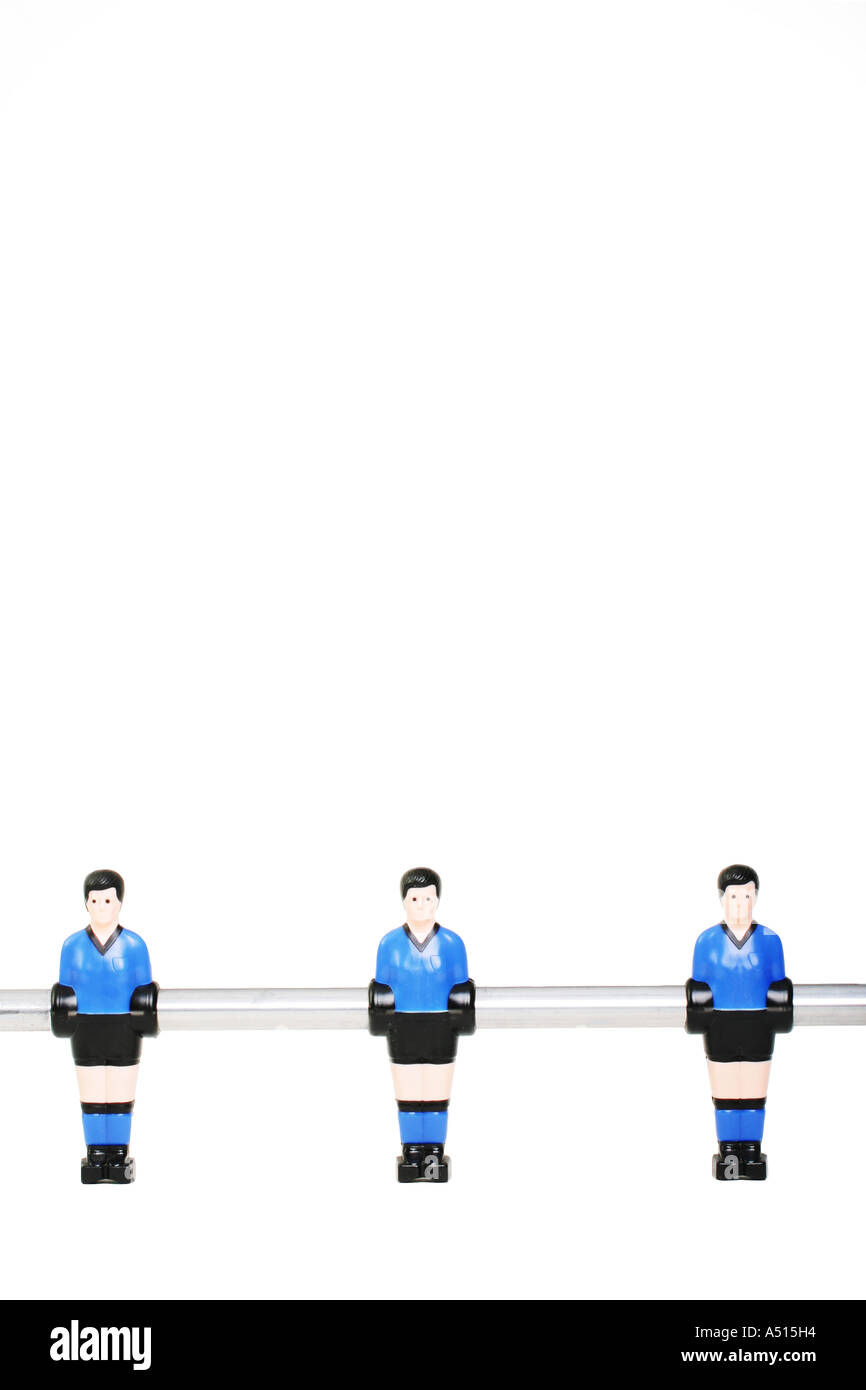 Three football players from a table football game. - Stock Image