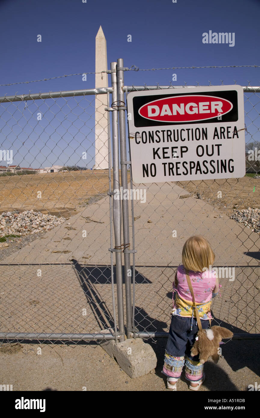 Small child looks through chain link fence into construction zone around the Washington Monument Washington DC USA - Stock Image