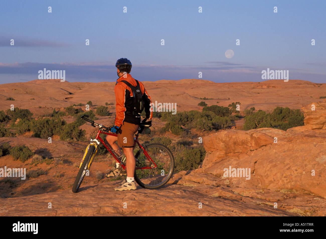 Moab UT Mountain biking on the Moab Slickrock Bike Trail Navajo Sandstone BLM land Full moon Stock Photo