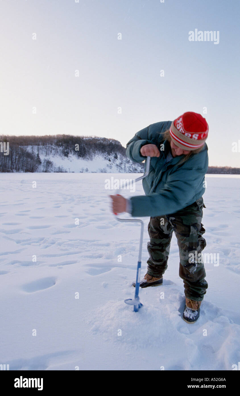 man drilling hole in ice over lake for ice fishing pond auger Stock