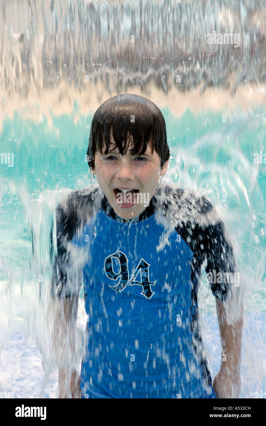 Young boy smiling in water fall waterfall cooling off at playground in summer.  Properties of water.  Water is a - Stock Image