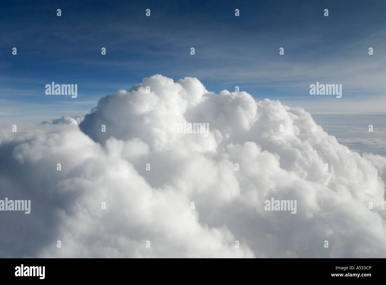 Puffy white cumulus clouds close up from airplane with blue sky - Stock Image