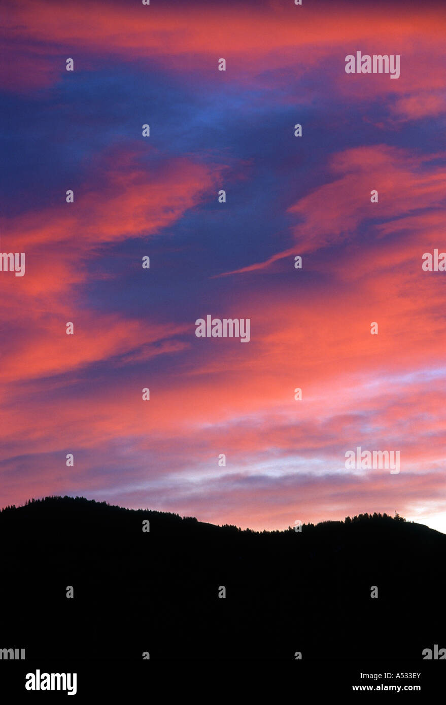 Brilliant sunset clouds over mountain ridges - Stock Image