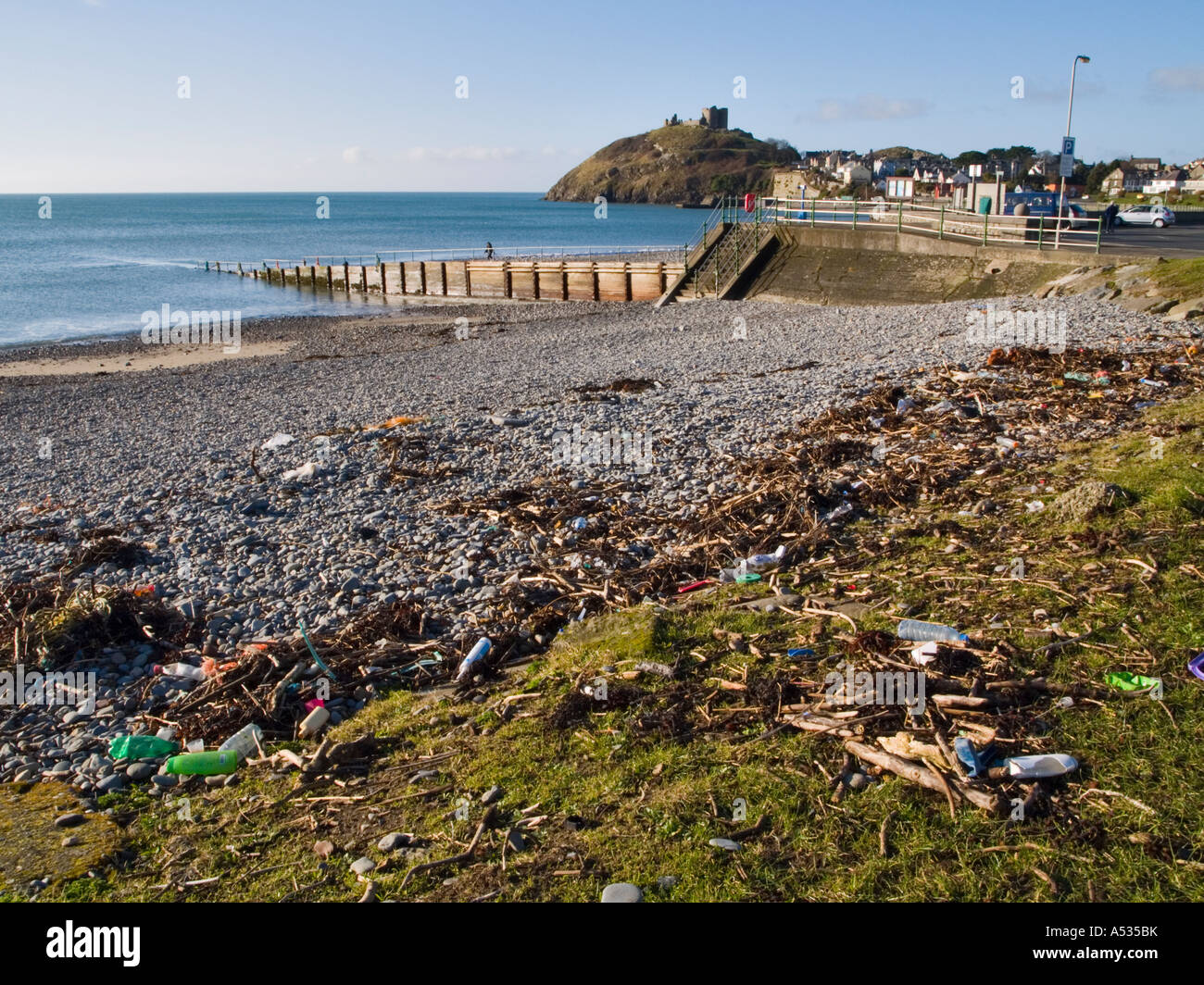 Flotsam and jetsam rubbish on beach littered with plastic bottles cans nylon rope washed up on shore Criccieth Gwynedd - Stock Image