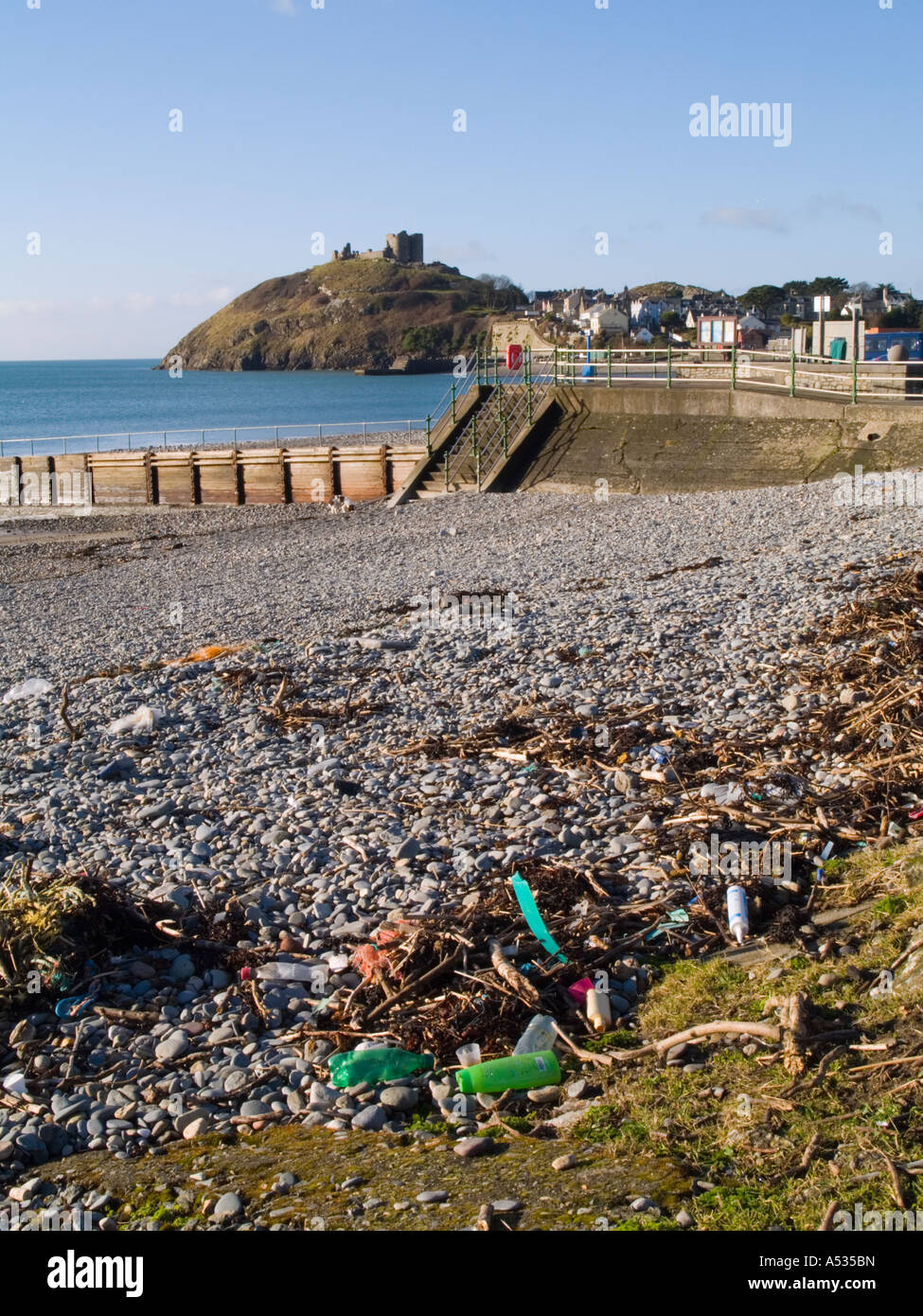 Flotsam and jetsam rubbish on a beach littered with plastic bottles cans nylon rope washed up on shore Criccieth - Stock Image