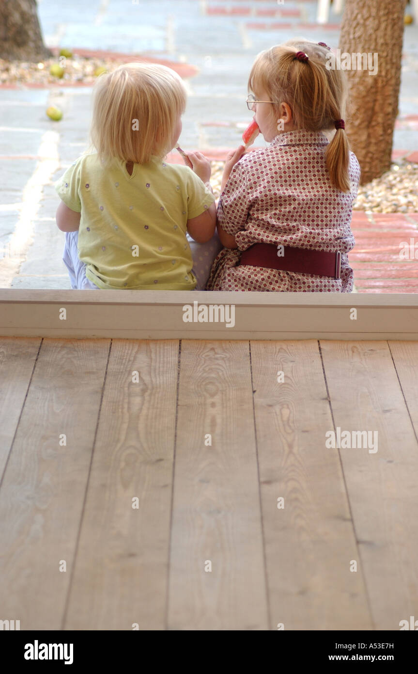 Two British friends girls talking with sweets  in nursery London UK - Stock Image