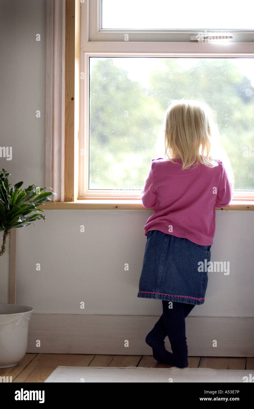 British infant looking out of window at home London UK - Stock Image