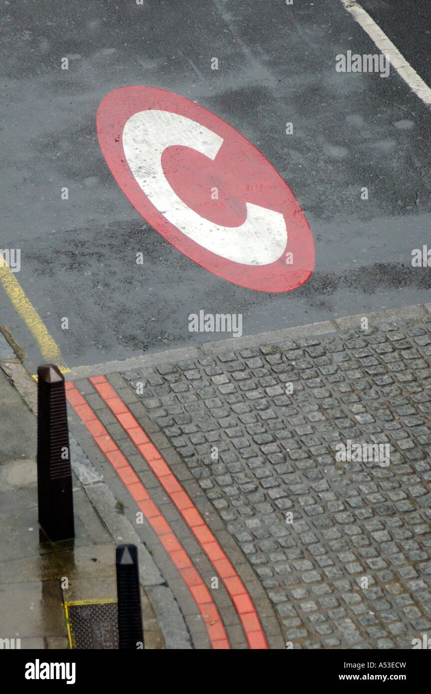 Photograph of British congestion zone symbol and logo painted on the tarmac, road surface in central London UK - Stock Image