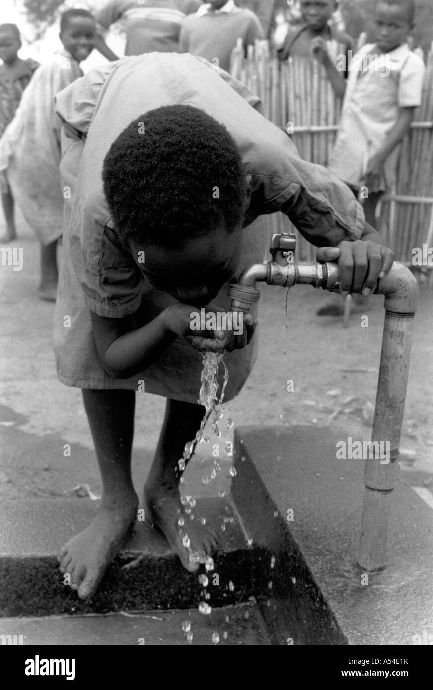 Painet hn1968 563 black and white water boy drinking village spout rwanda country developing nation less economically - Stock Image