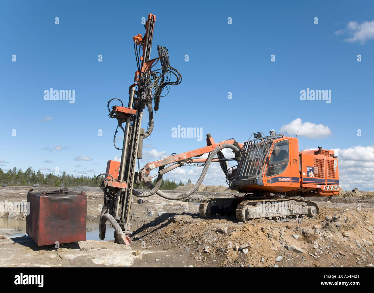 Orange Tamrock Ranger 780 rock drill machine in a rock