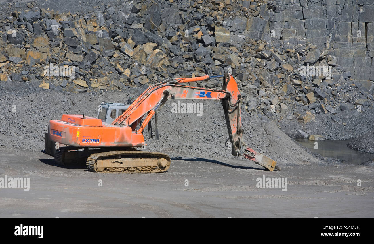 An orange excavator at the bottom of a rock quarry equipped with rock hammer , Finland Stock Photo