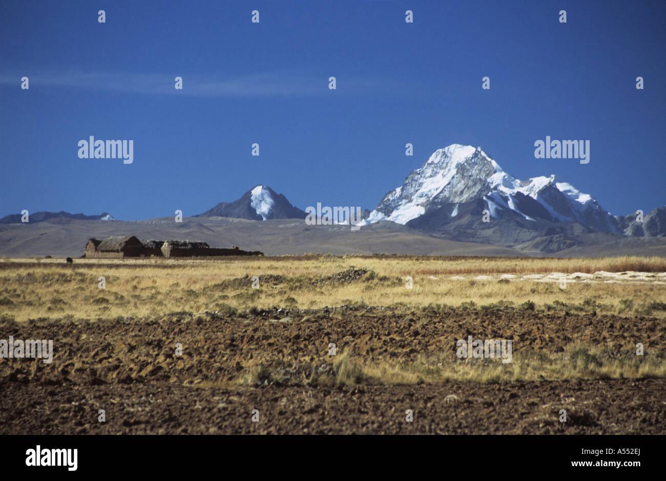 Mt Huayna Potosi and farm on altiplano near Laja, Cordillera Real, Bolivia - Stock Image
