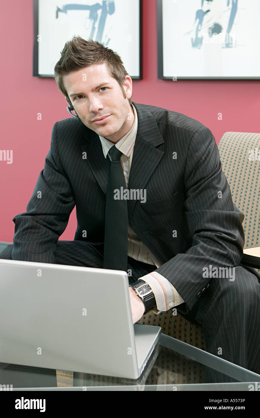 Businessman using laptop and hands free device - Stock Image