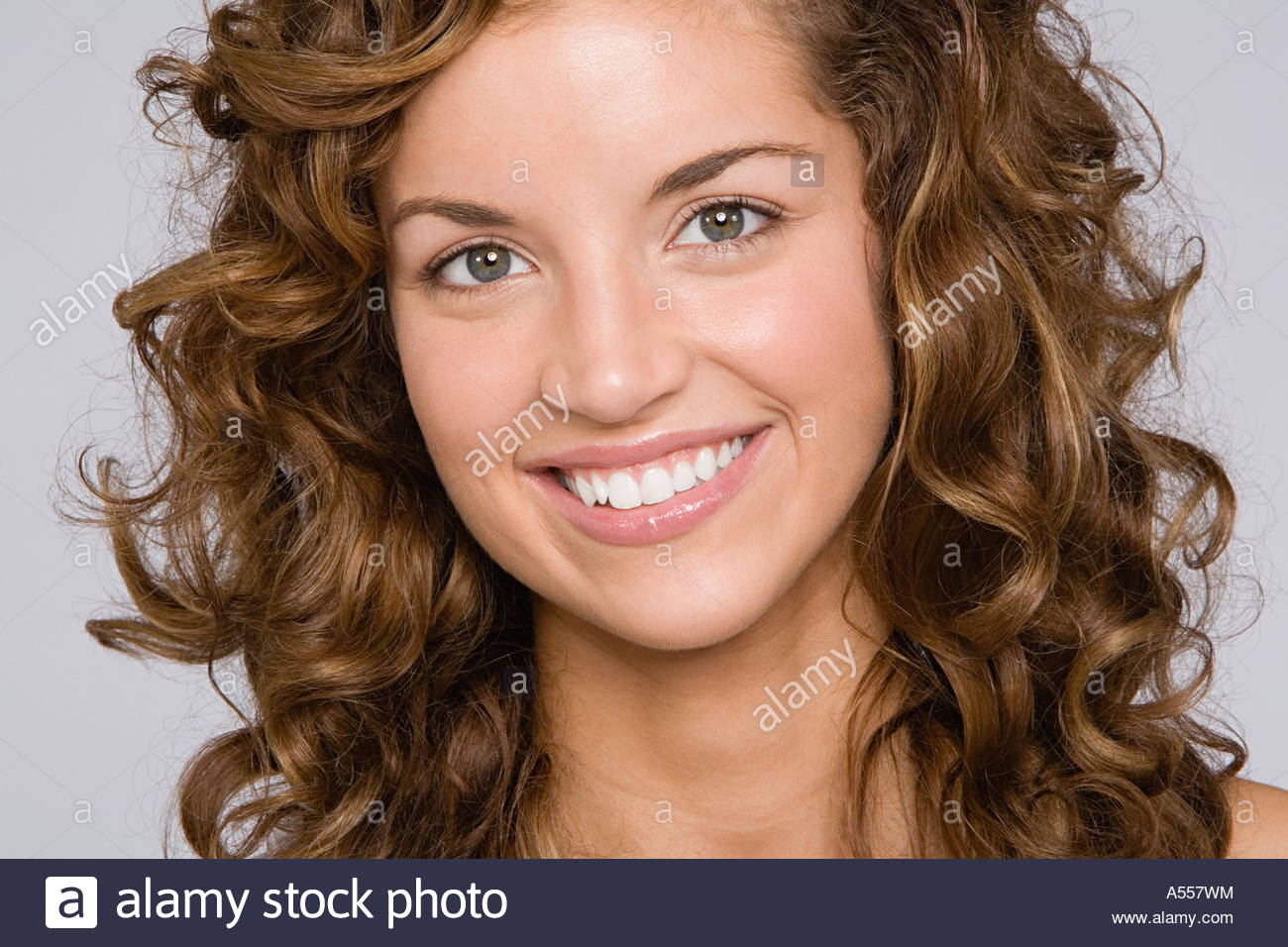 Portrait of a curly haired young woman - Stock Image