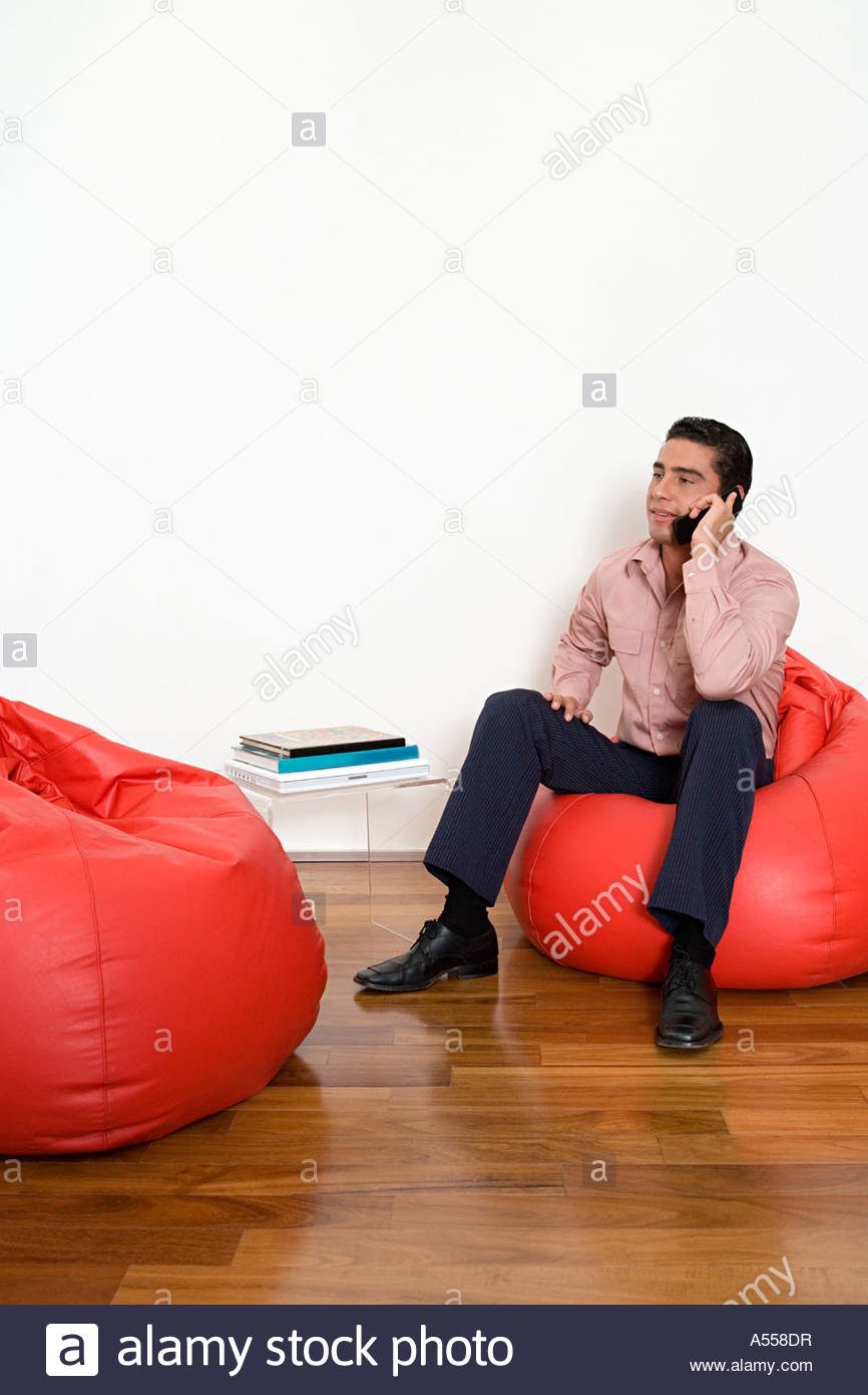 Office worker sitting on a red beanbag - Stock Image