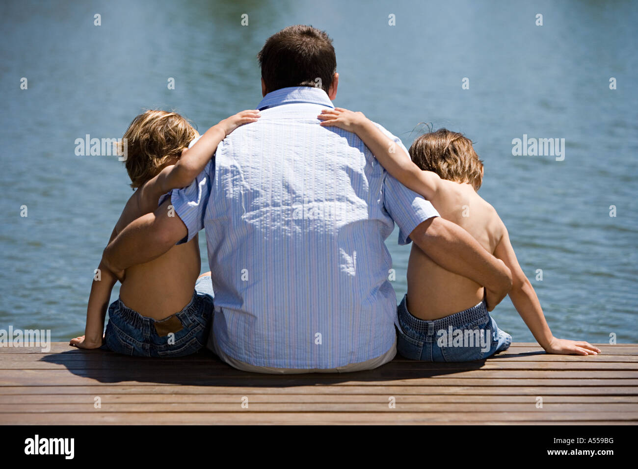 Father and sons on a wooden pier - Stock Image