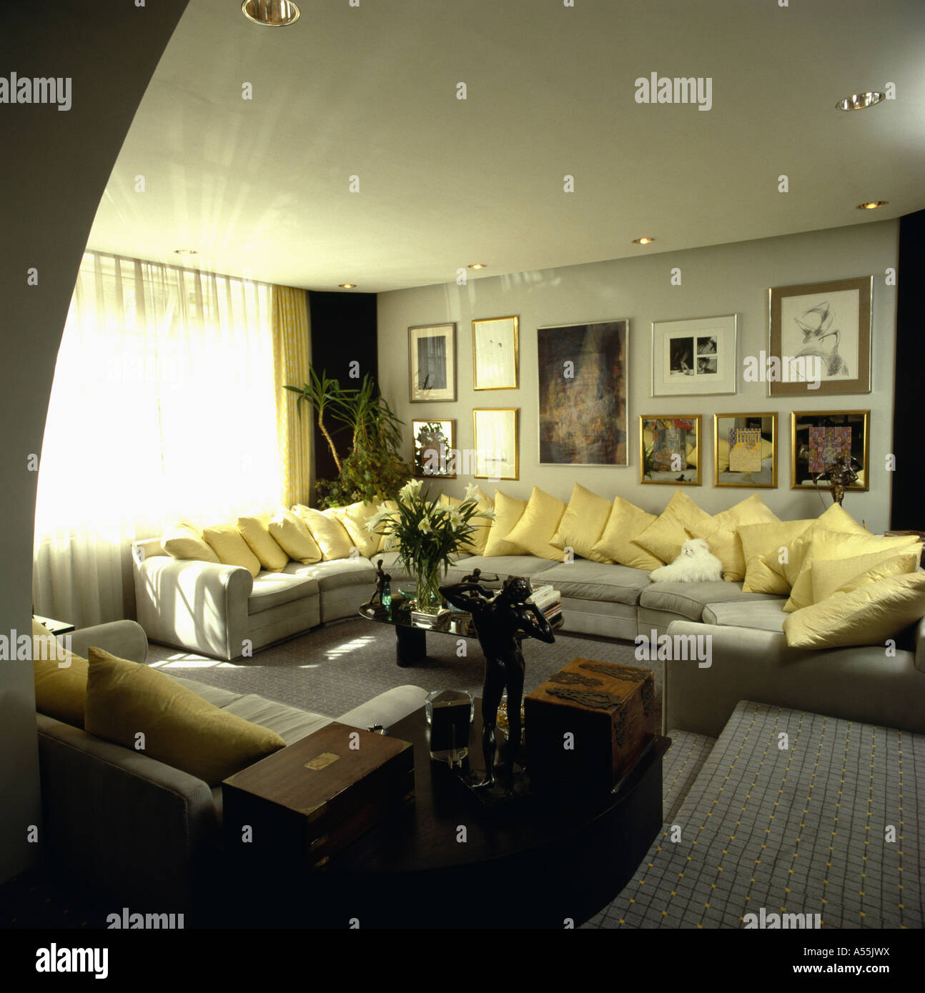 Pictures above large curved sofa with yellow cushions in ...