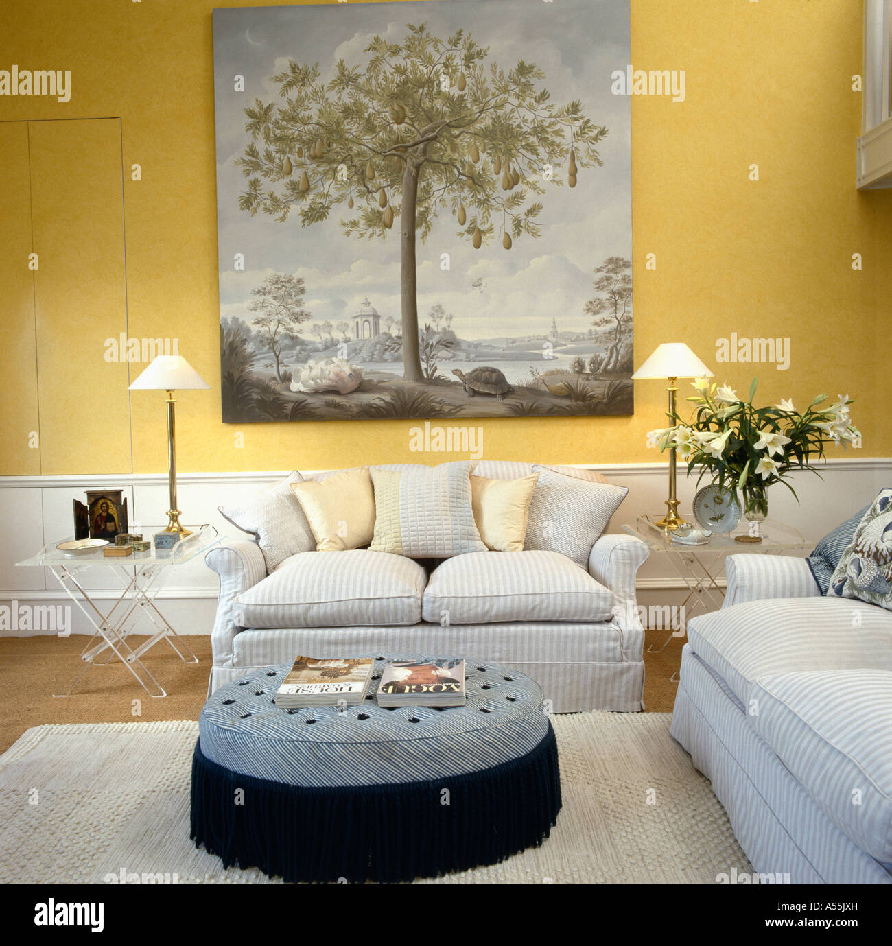 Large 18th Century Style Picture Above Pale Gray Sofa In Pale Yellow Living  Room With Large Circular Upholstered Stool
