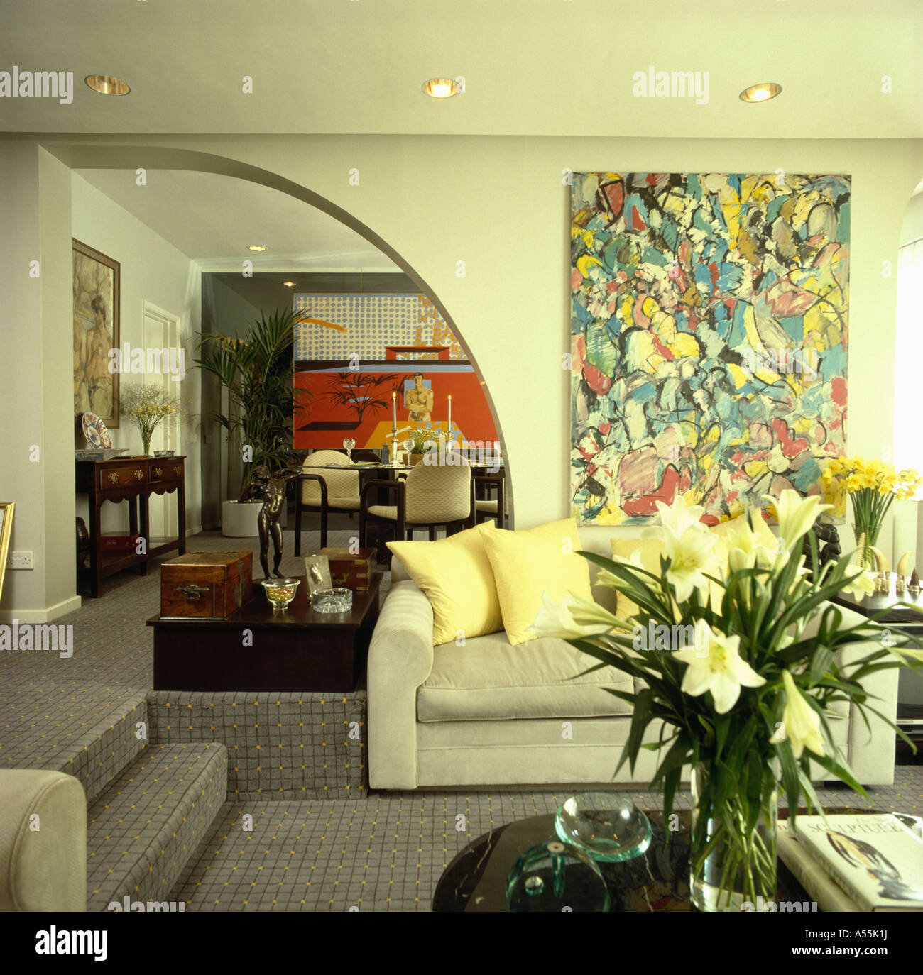 Large abstract painting on wall above pale gray sofa beside arched ...