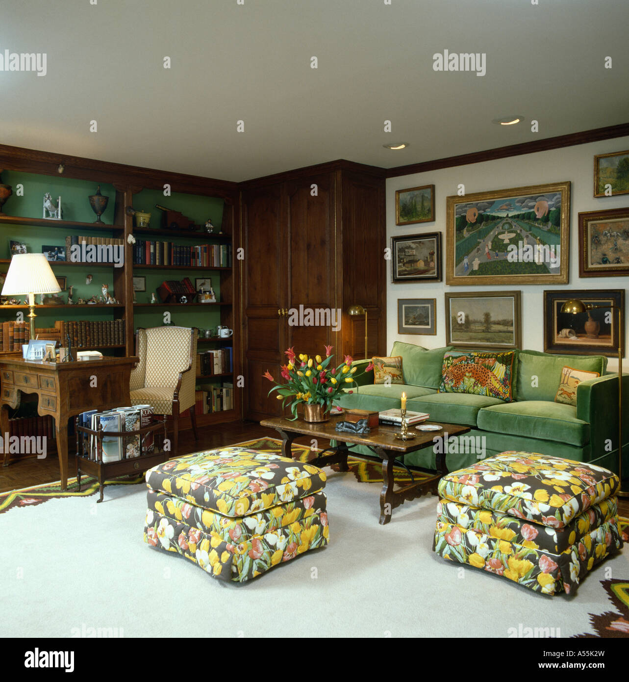 Floral print upholstered stools and green velour sofa below group of pictures in eighties living room with pale gray carpet