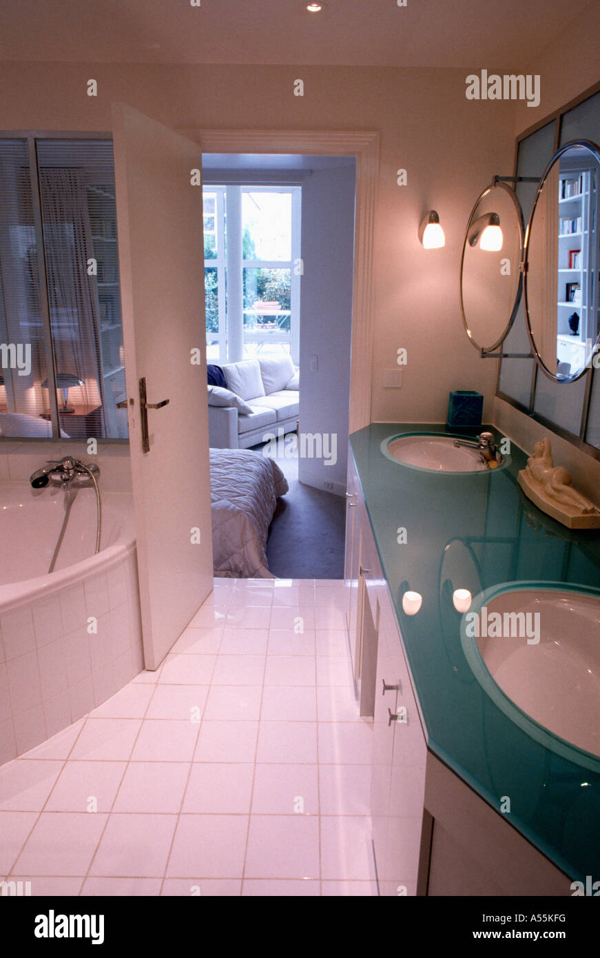 Double basin in glass vanity unit in modern ensuite bathroom with white tiled floor - Stock Image