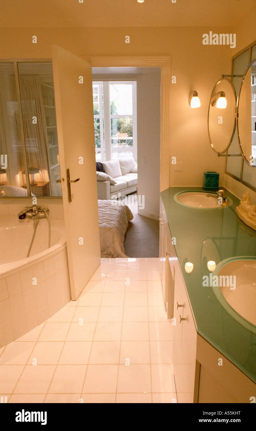 Basins set into glass vanity unit in modern ensuite bathroom with white tiled floor and open door to bedroom - Stock Image