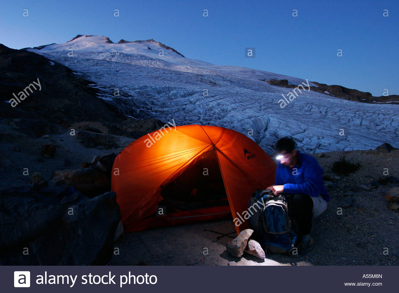Young man gets ready for tomorrow s climb MSR Hubba Hubba Easton Glacier railroad grade Mt Baker Wilderness Washington - Stock Image