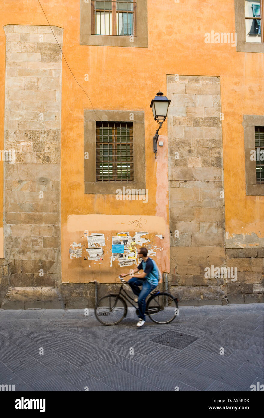 Yellow ochre wall and passers by Pisa Tuscany Italy - Stock Image