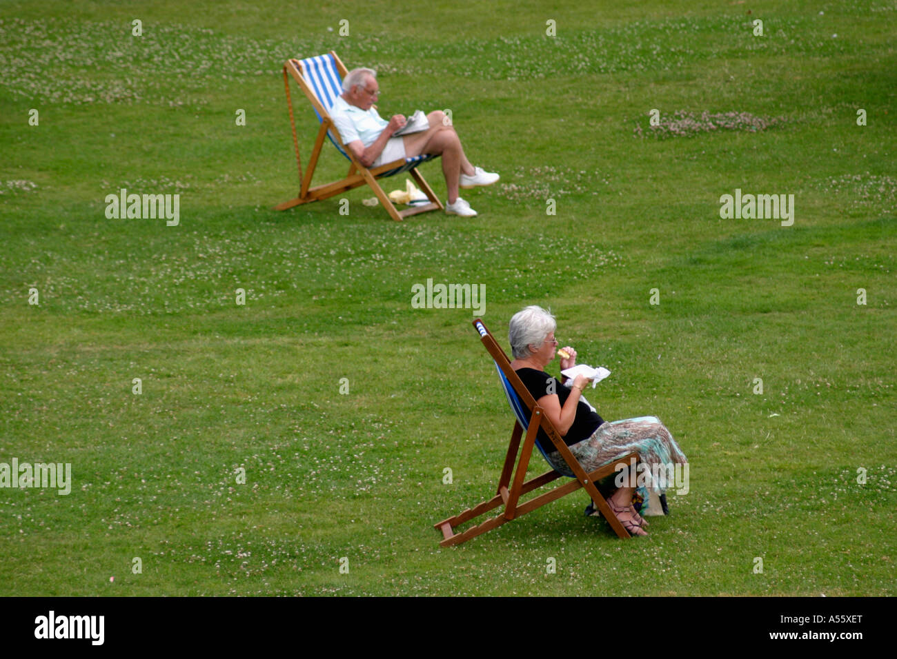 two old people sitting on deck chairs in a park Stock Photo ...