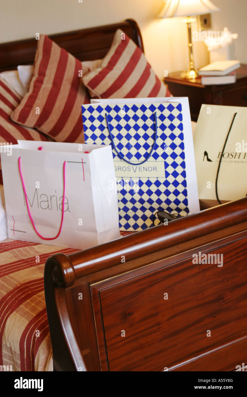 shopping bags on hotel bed. - Stock Image