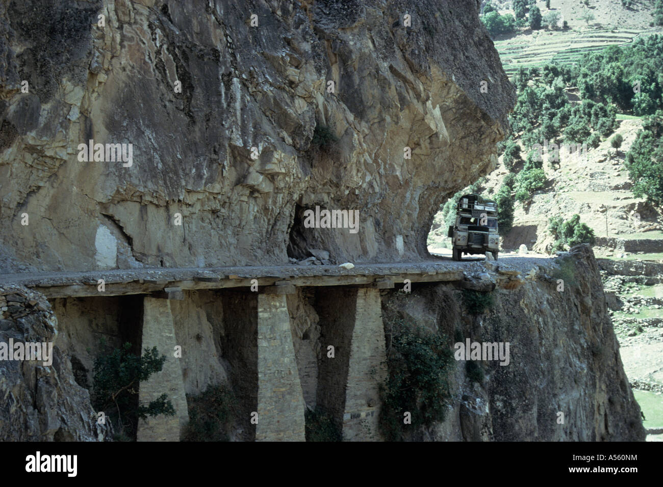 Land Rover Series III approaching Chitral with low overhangs and the road supported from below Dir to Chitral Northwest - Stock Image
