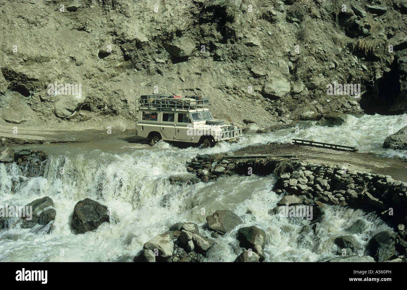 Land Rover Series III crossing a fast flowing glacier melt river Lowarai Pass Dir to Chitral Northwest Pakistan - Stock Image