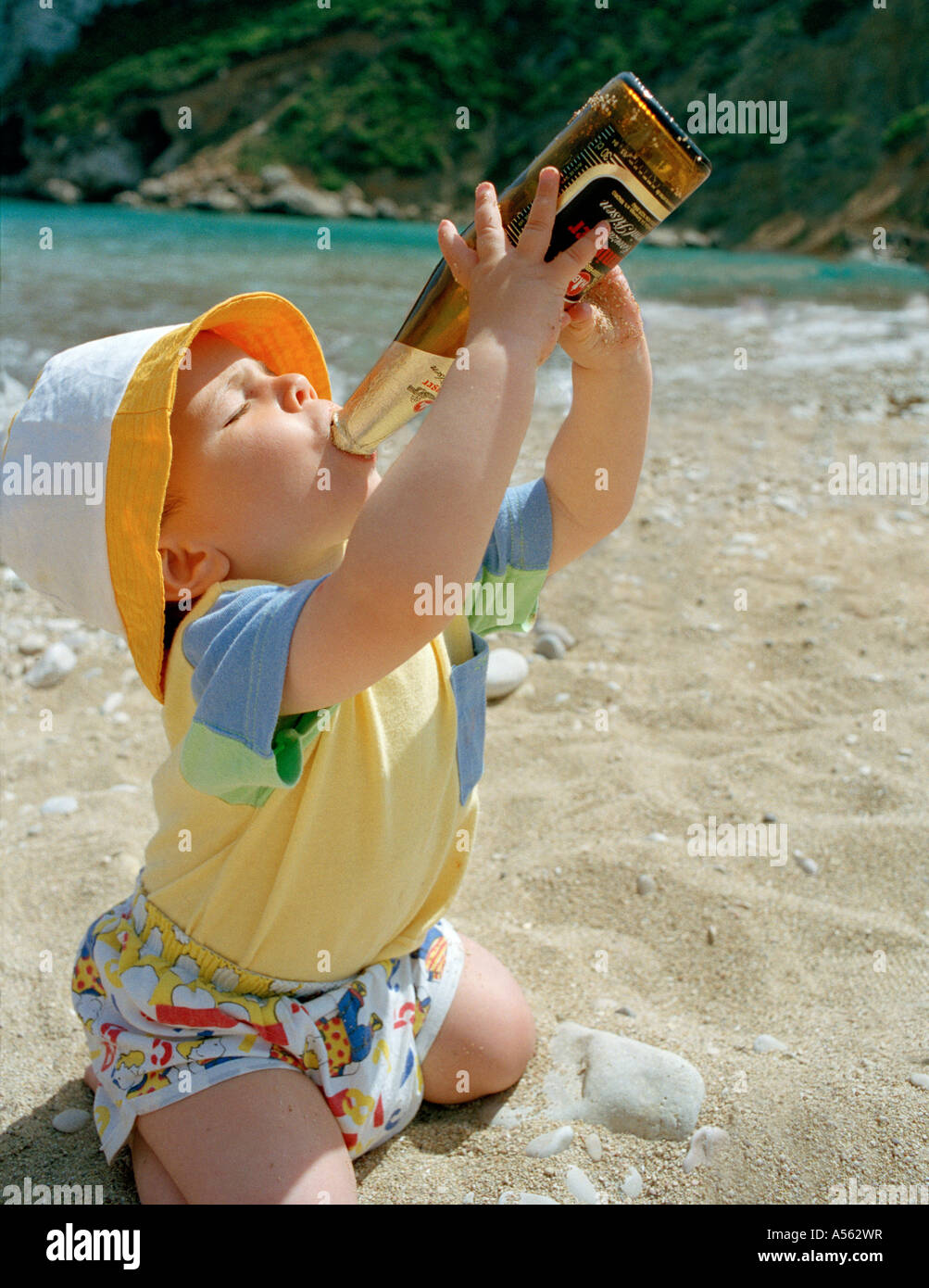 Baby boy trying to drink beer on a beach. - Stock Image