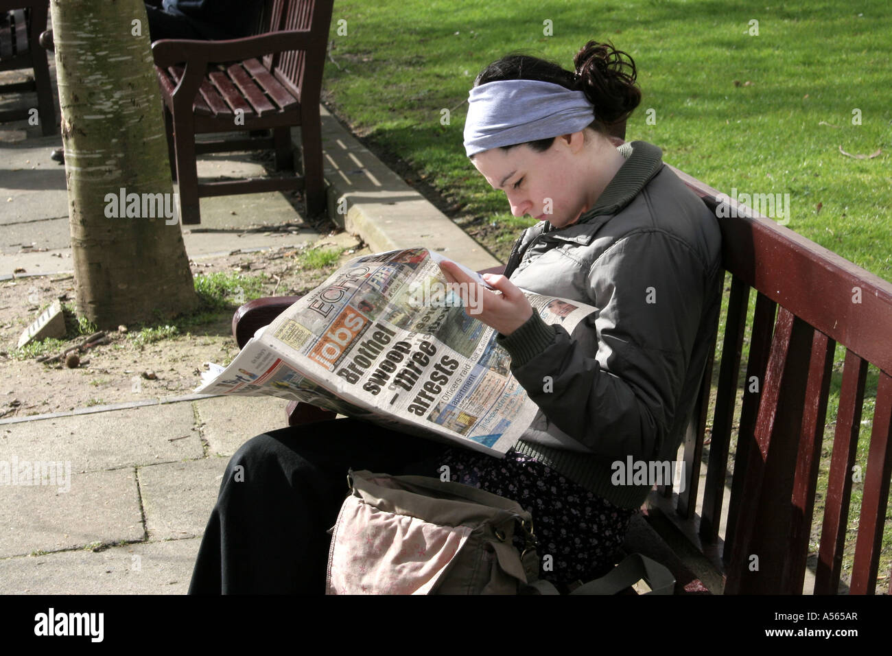 A woman reading the job section of a newspaper, sat on a park bench in the UK. - Stock Image