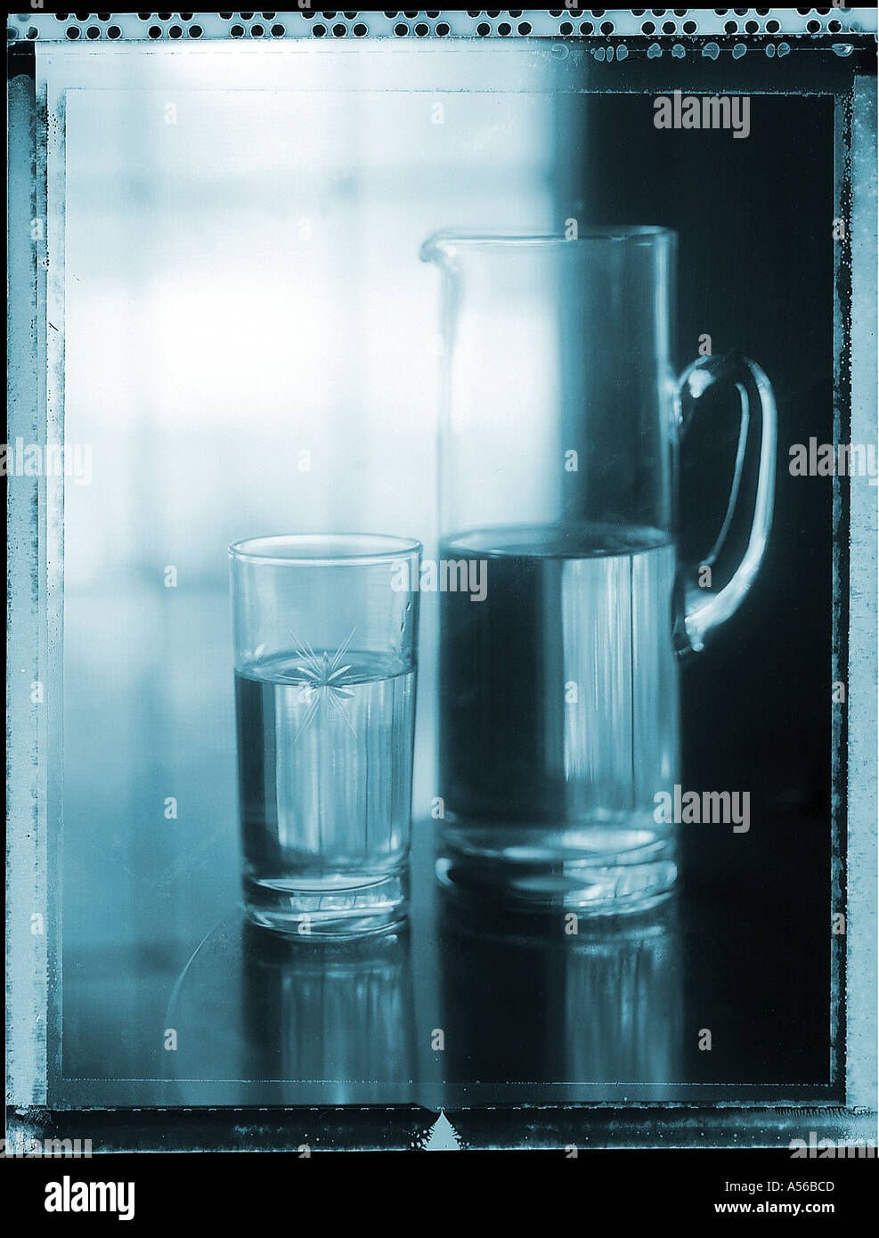 Half full glass of water and pitcher of water on table near window - Stock Image