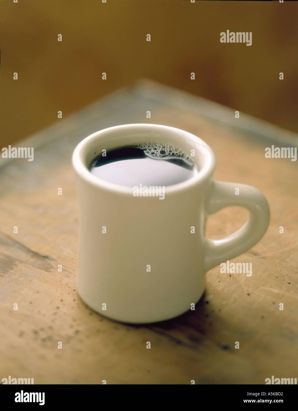 Mug of coffee sitting on corner of table - Stock Image