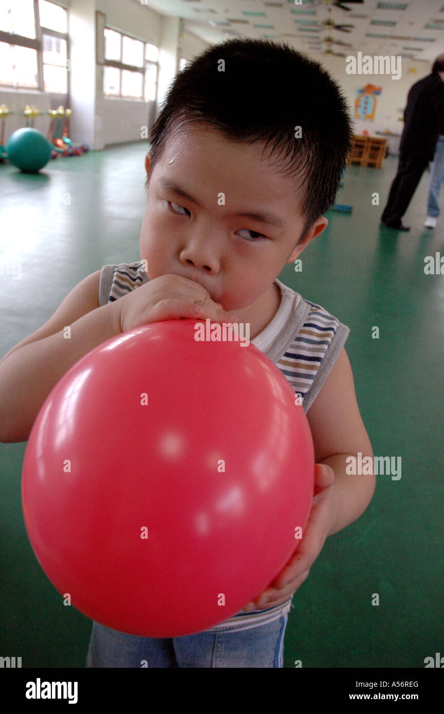 Painet ja0789 boy kid child blowing balloon taiwan catholic primary school taichung photo 2004 asia china chinese - Stock Image