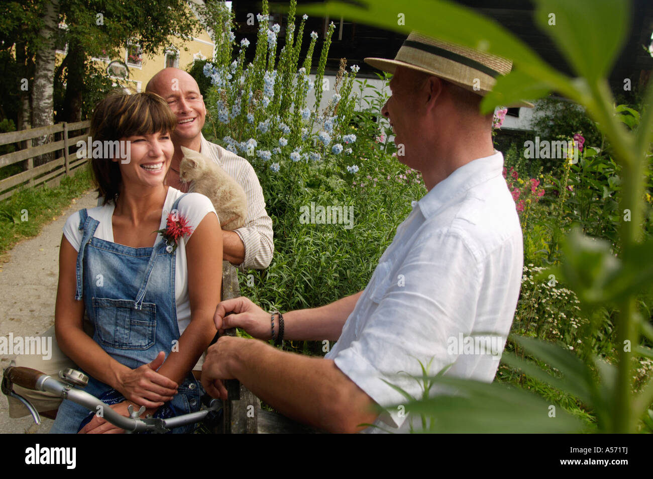 Couple sitting on bicycle, talking to neighbor - Stock Image