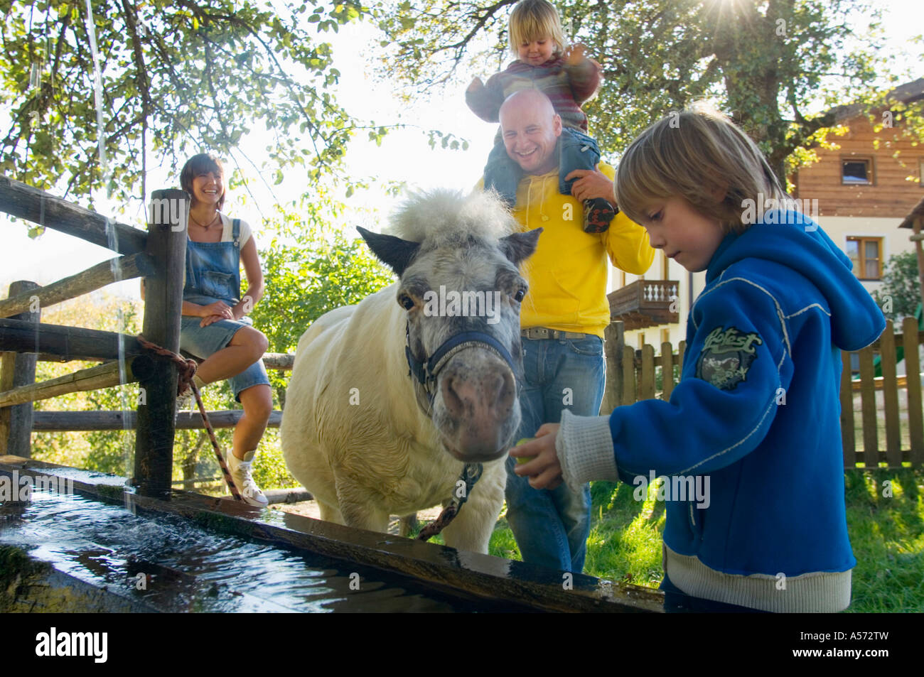 Family watching pony at fountain - Stock Image