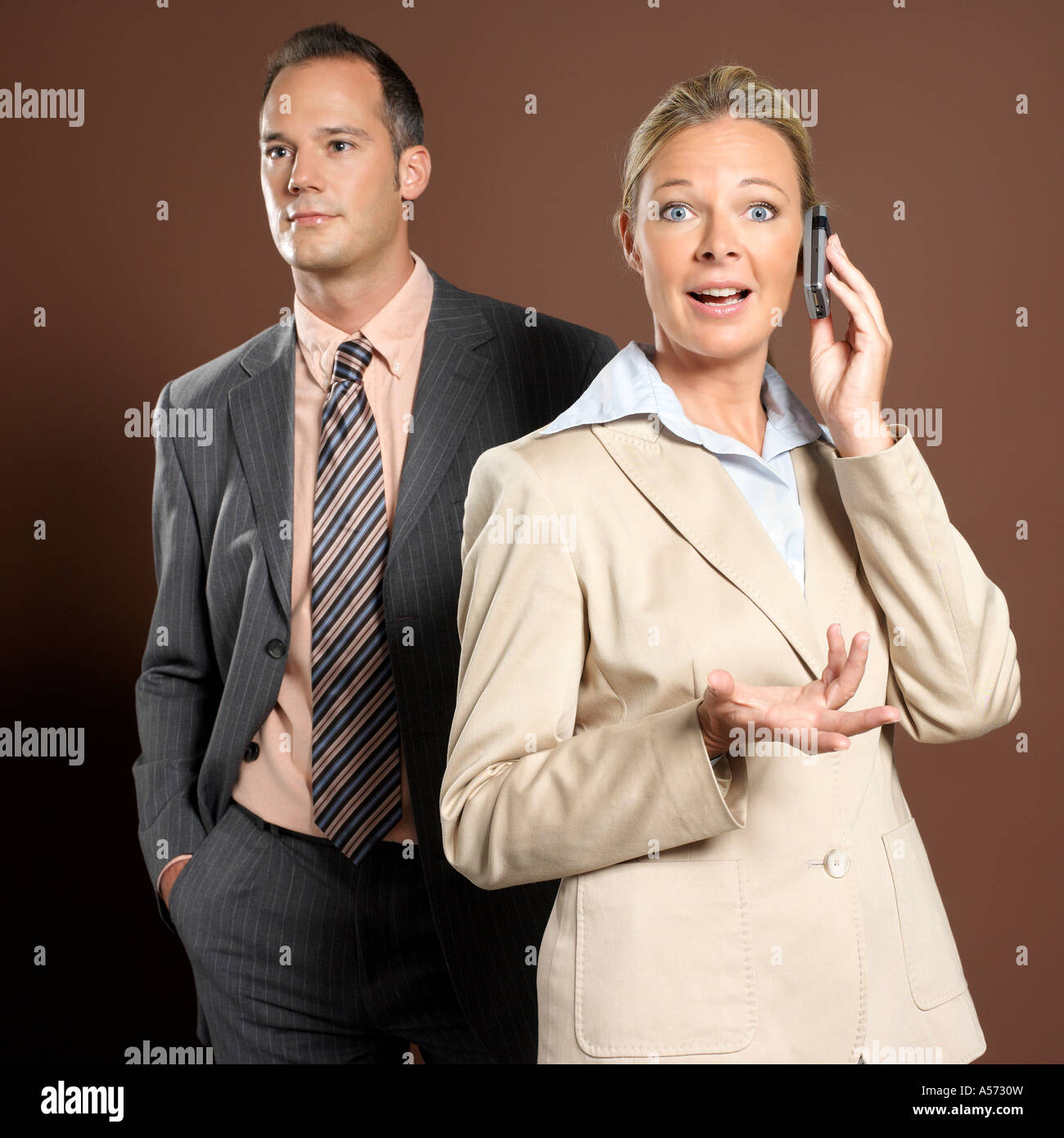 Businessman and businesswoman, woman holding mobile phone - Stock Image