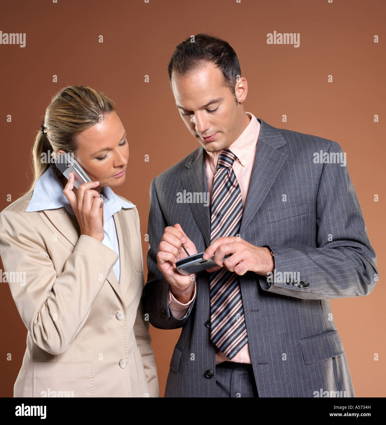 Businessman and woman using mobile phone and palmtop - Stock Image
