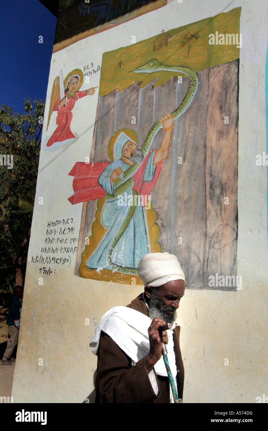 Painet jb1235 ethiopia priest walking passed mural depicting abuna aregawi serpent kidana merhet church tigray africa - Stock Image