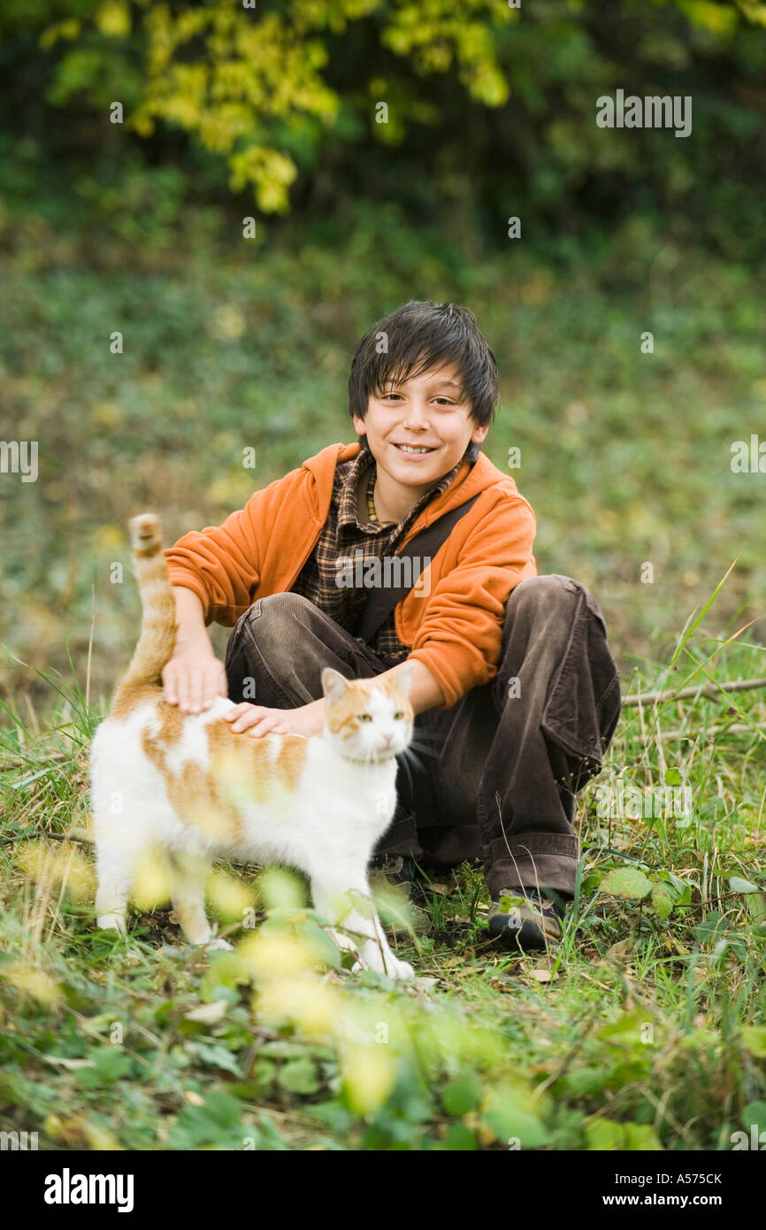 Boy (13-15) sitting in meadow petting cat - Stock Image